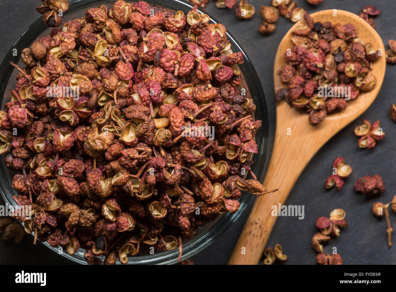 Szechuan Peppercorns in Glass Bowl with Spill Over in wooden spoon Stock Photo
