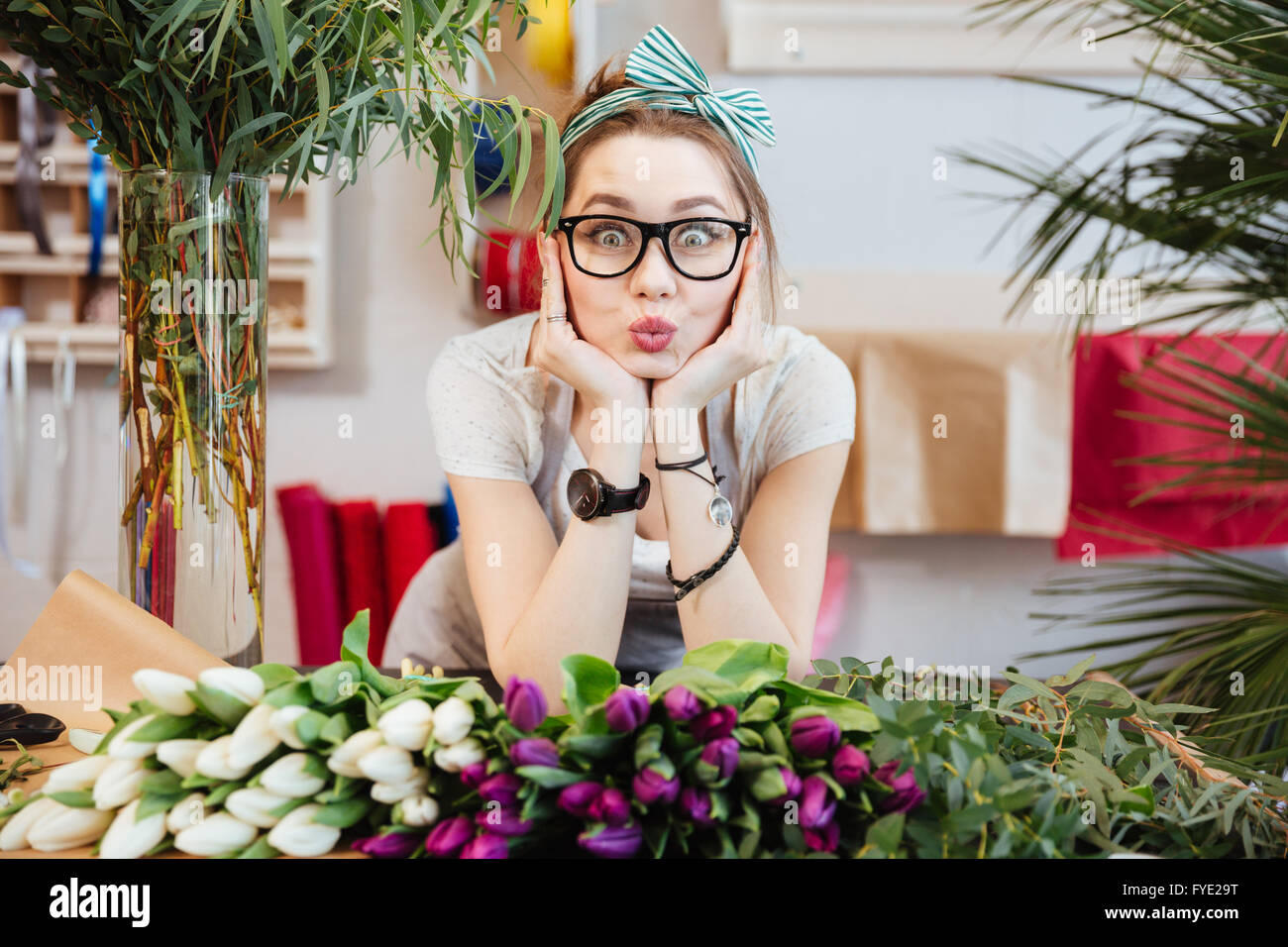 Portrait of charming amusing young woman florist making funny face standing in flower shop - Stock Image