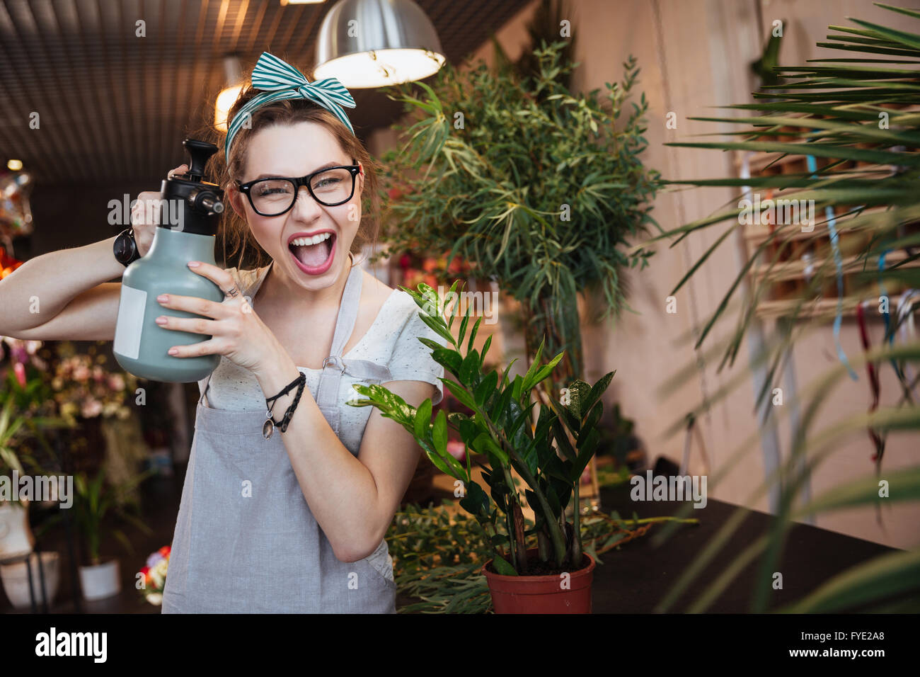 Funny pretty young woman florist watering flowers and pointing with water sprayer on you - Stock Image