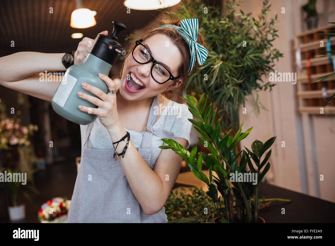 Amusing young woman florist with water sprayer watering flowers and shouting - Stock Image