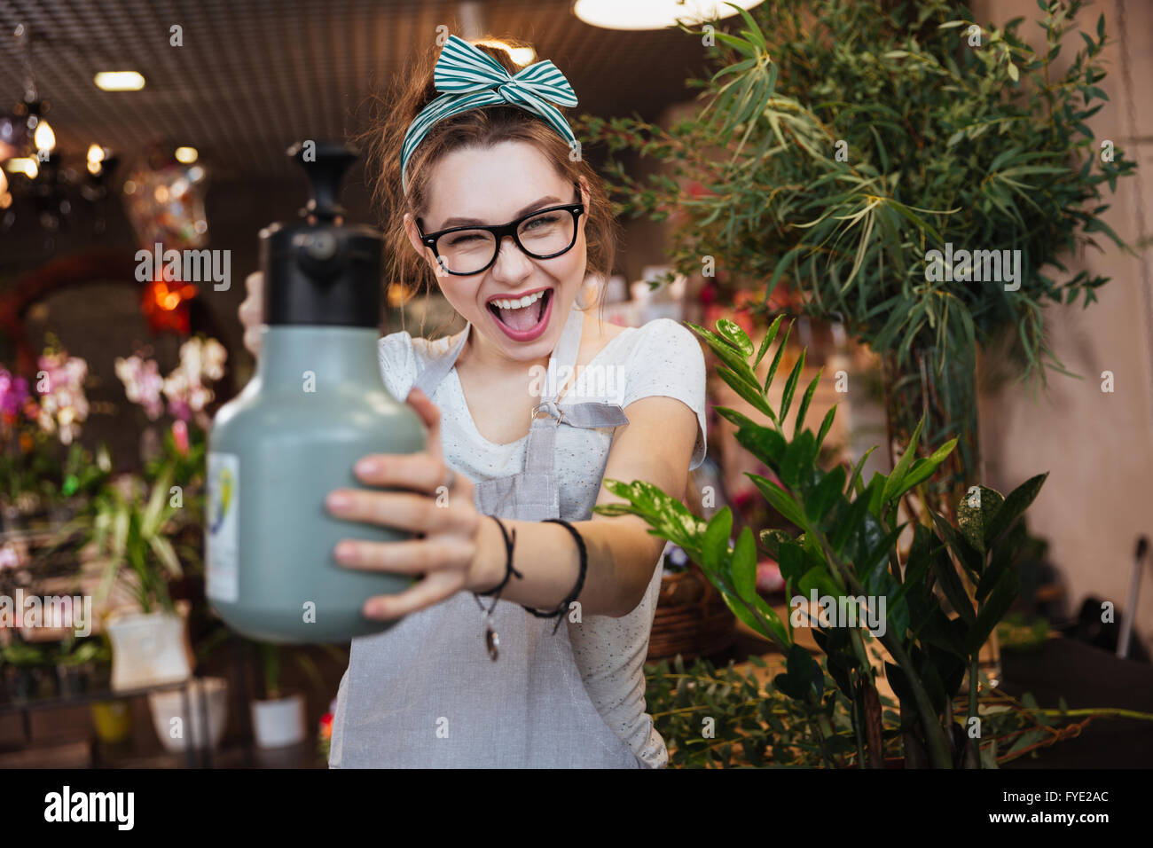Playful attractive young woman florist pointing with water sprayer on you in flower shop - Stock Image