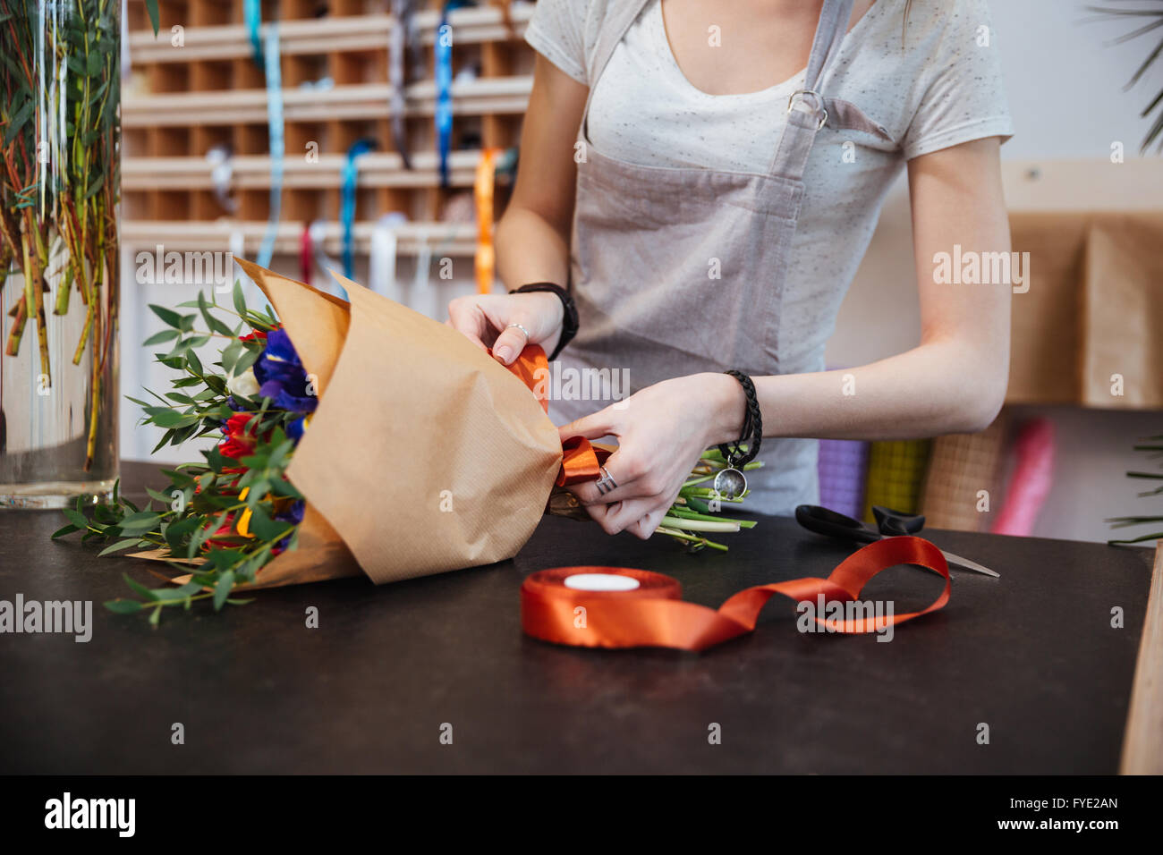 Hands of young woman florist standing and making bouquet of flowers in shop - Stock Image