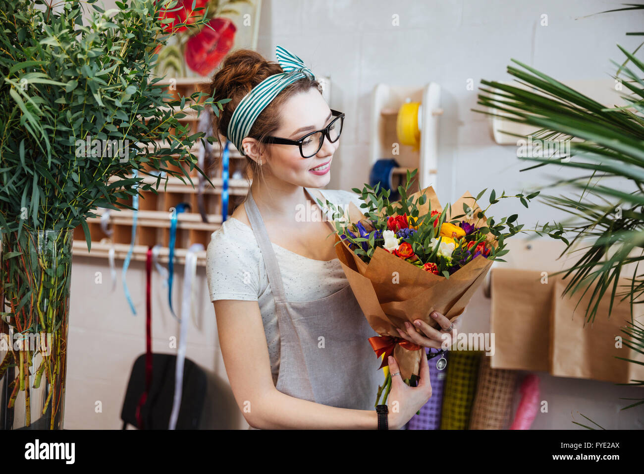 Smiling attractive young woman florist standing and holding bouquet of flowers in shop - Stock Image