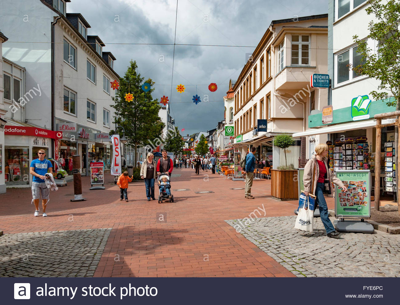 People shop and brows the stores on Stadtweg in the city of Schleswig, Germany. - Stock Image