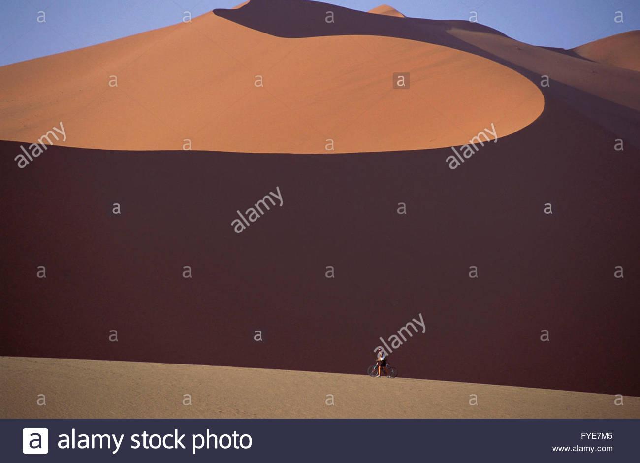 Riding bicycle on Sossusvlei dune Namibia. - Stock Image