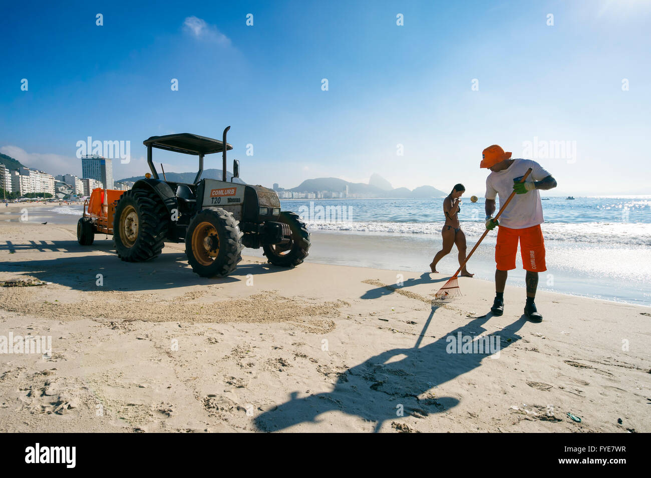 RIO DE JANEIRO - APRIL 3, 2016: Workers from the municipal COMLURB maintenance company clean Copacabana Beach before - Stock Image