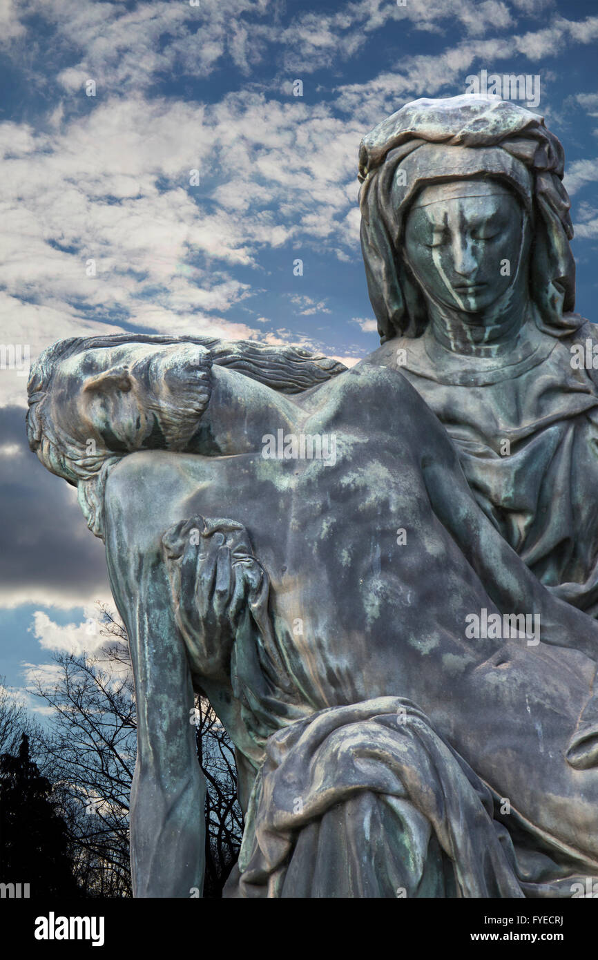 Bronze statue of Virgin Mary holding the body of Jesus Christ with sunset landscape at background. It´s called - Stock Image