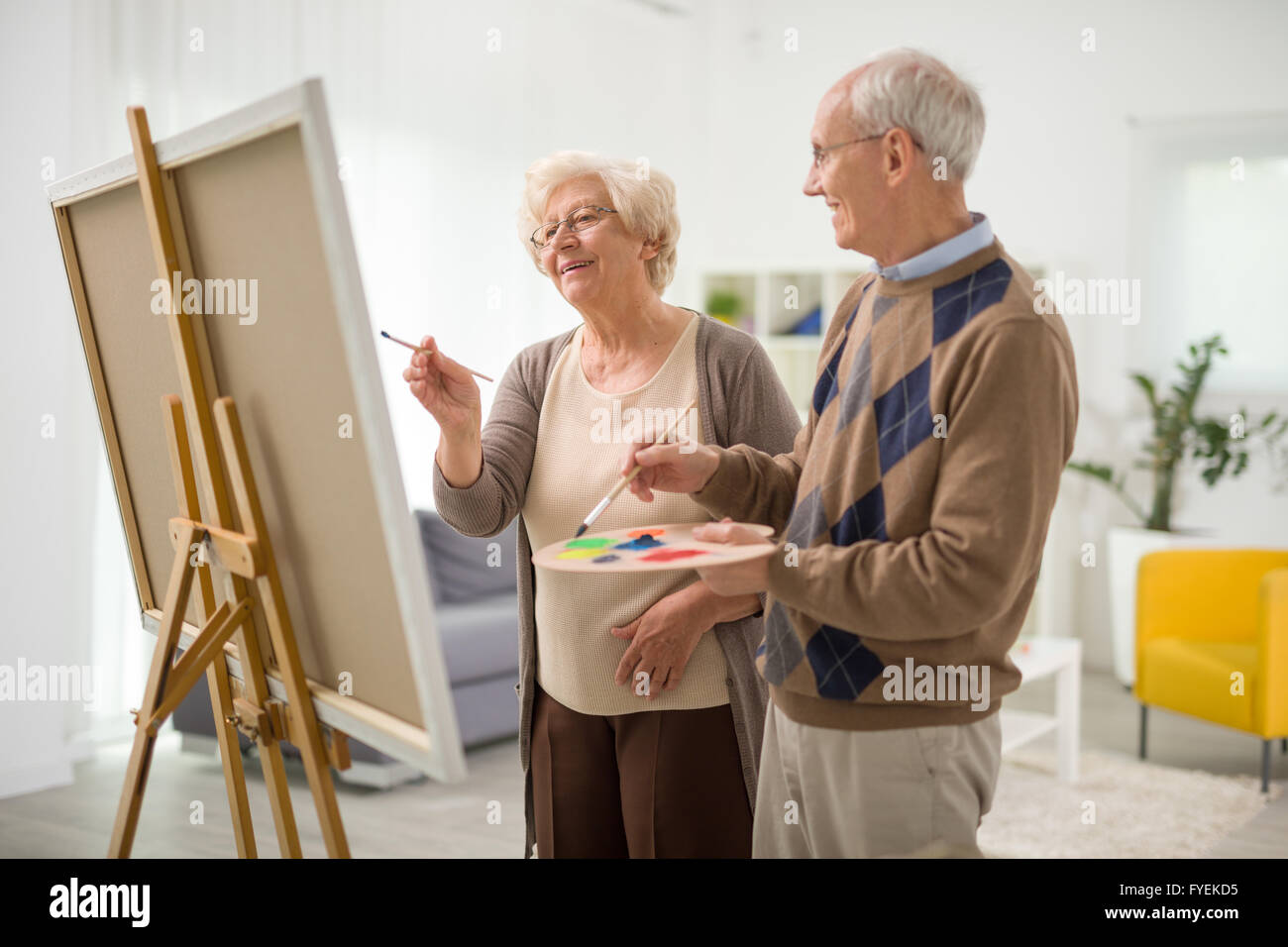 Elderly Couple Having Fun Together And Painting On A Canvas At Home