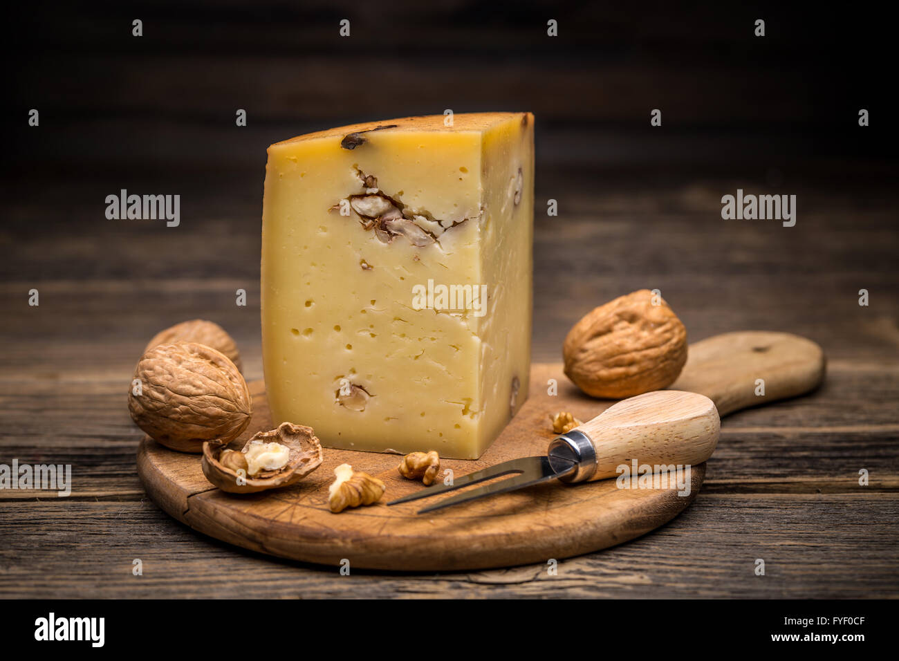 Piece of cheese with walnuts on wooden board - Stock Image