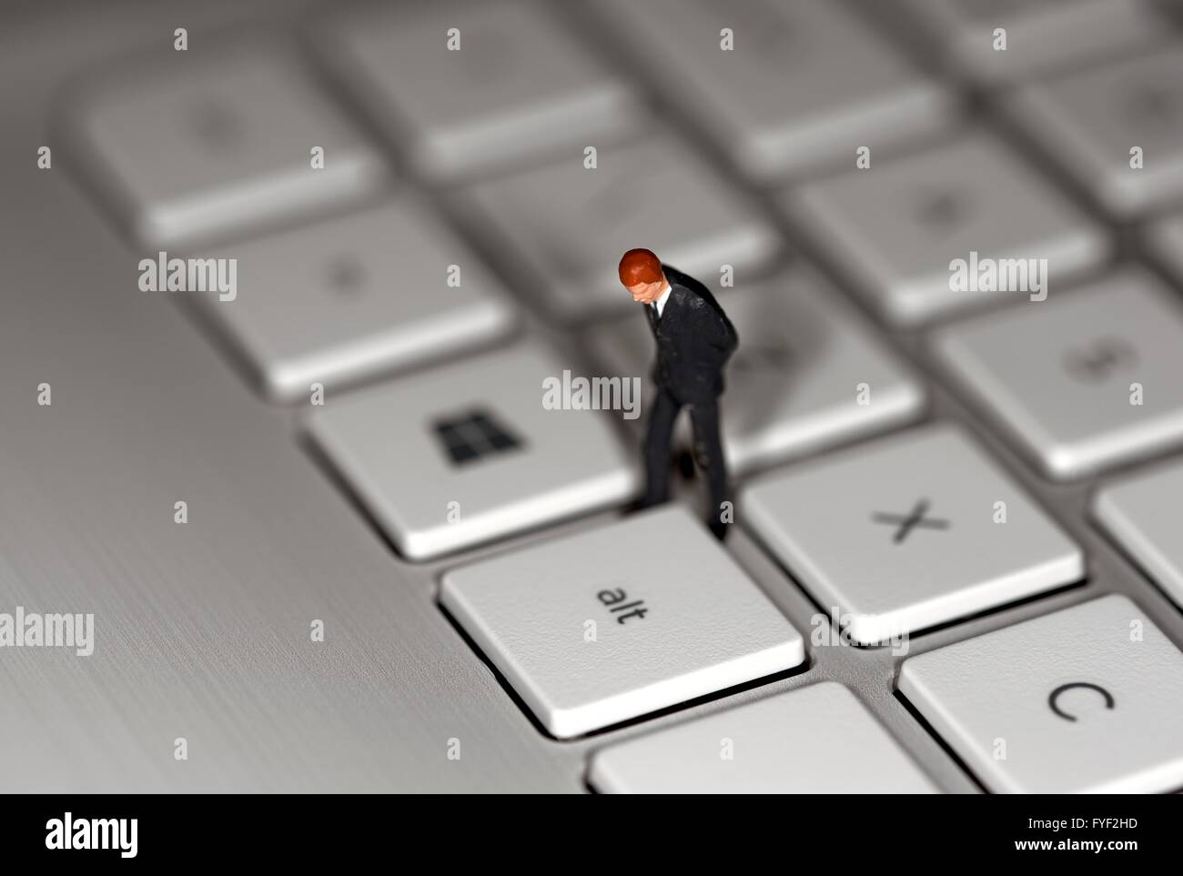 A miniature figurine business man standing on a laptop keyboard - Stock Image