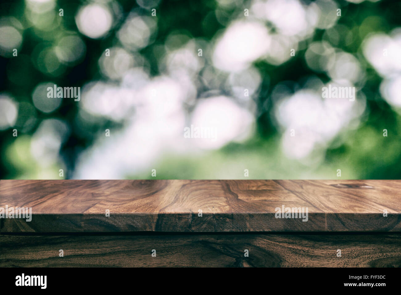 Empty top wooden table and floral blurred background - Stock Image