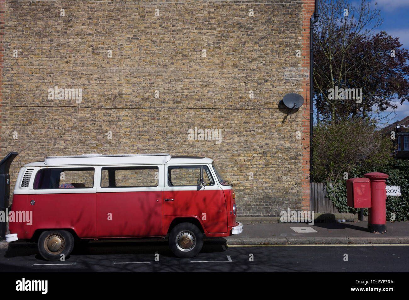 A parked red VW camper van parked next to a faded red Royal Mail postal box on a residential street in Herne Hill, - Stock Image