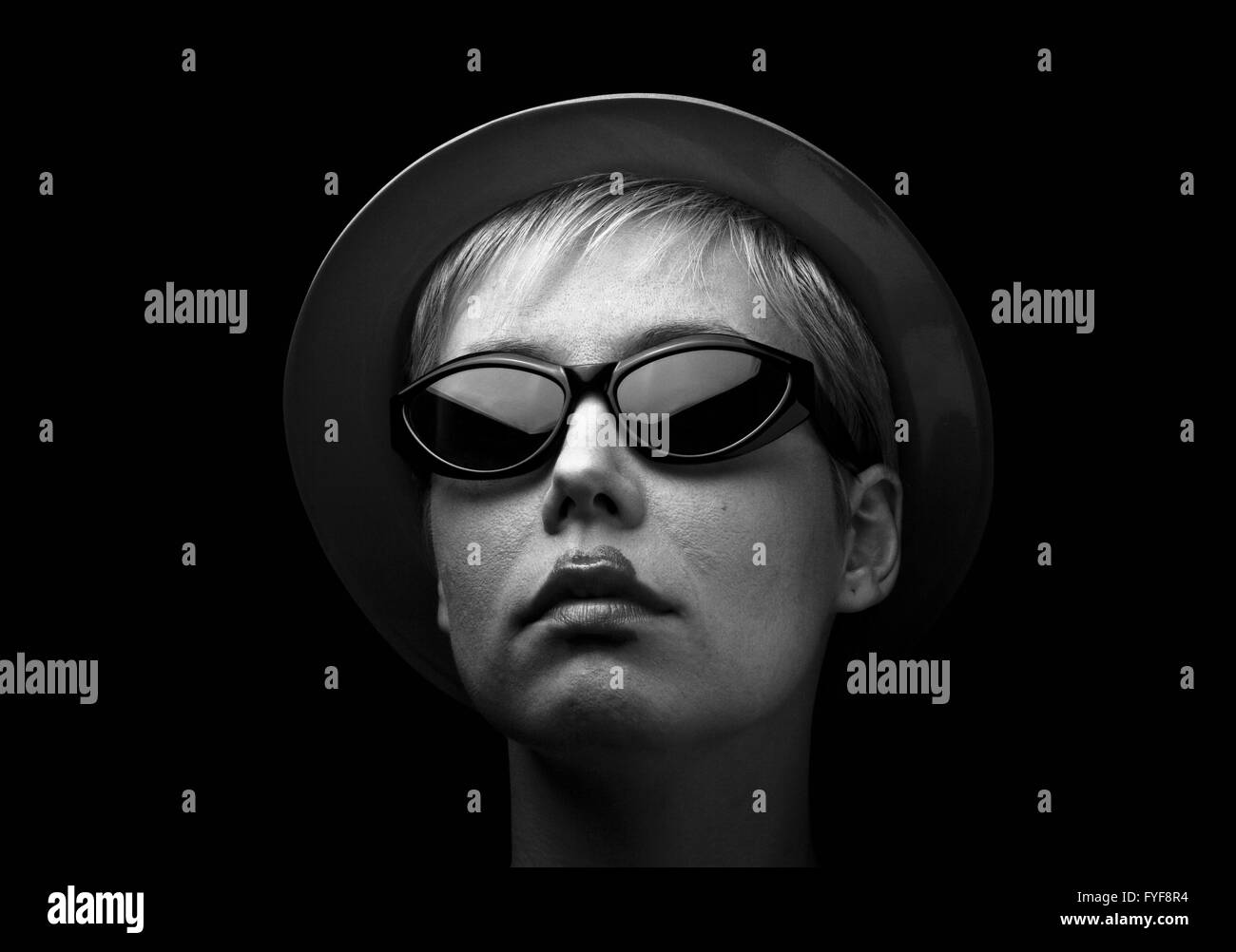 Horizontal portrait of a blonde woman with hat and black glasses on black background - Stock Image