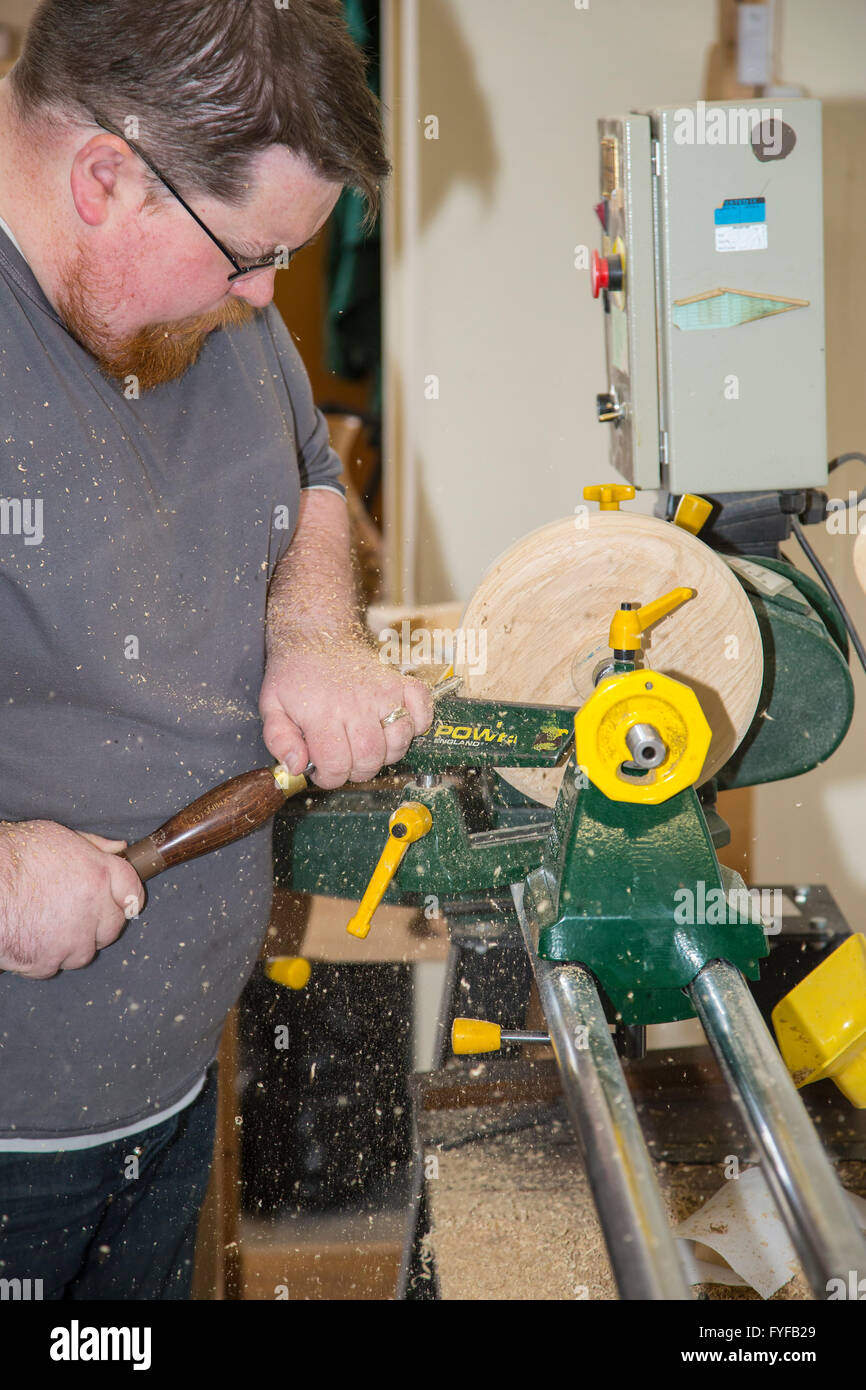 Woodturning craftsman at work turning wood on a woodturning lathe - Stock Image