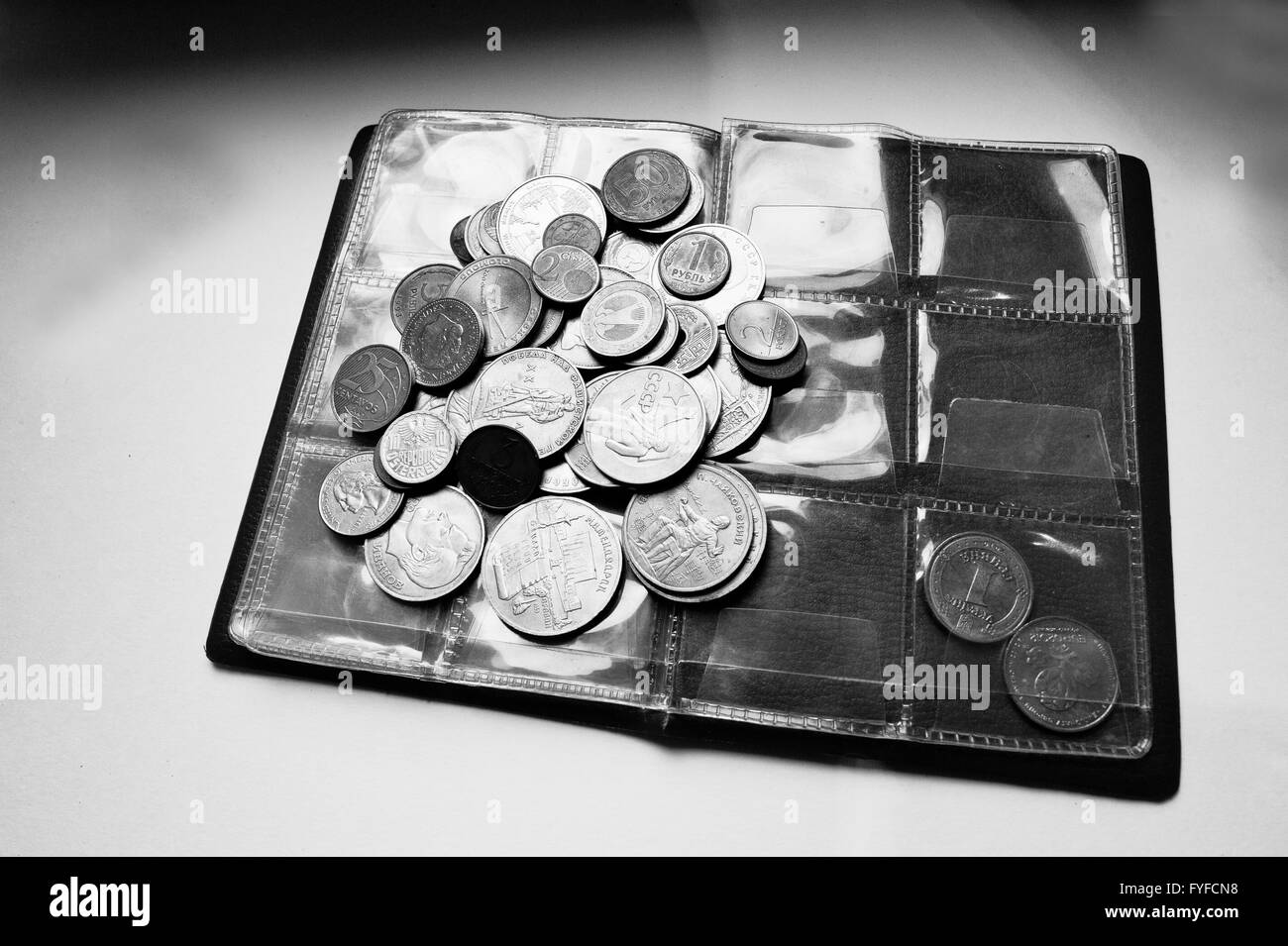 Different countries coins at umismatics album. Black and white photo - Stock Image