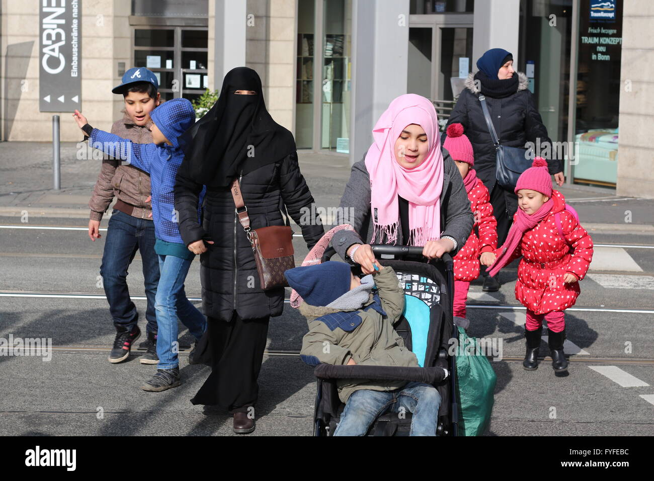 family of Refugees with Burka and kerchief on a street in Bonn, Germany - Stock Image