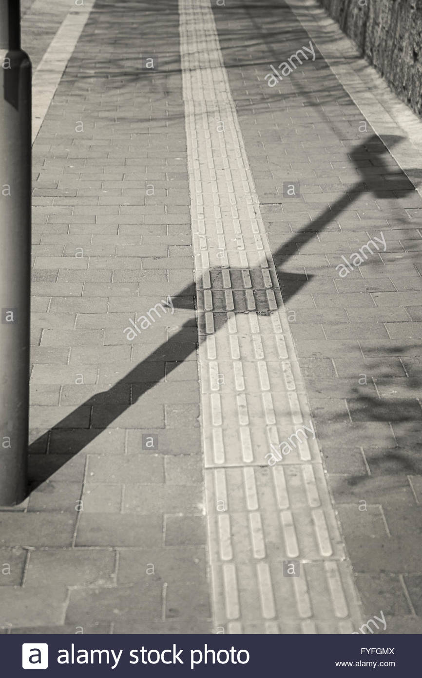 A shadow on the street with strait pavements - Stock Image