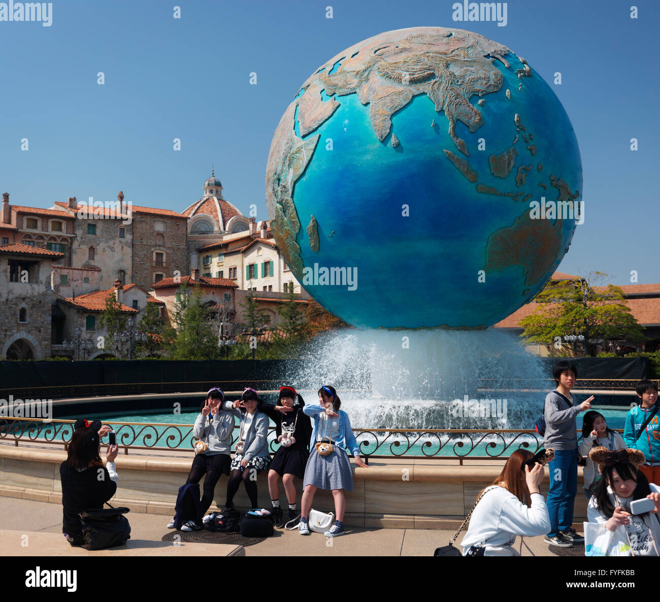 Girls posing for a photo at Earth globe fountain, Tokyo DisneySea, Tokyo Disney Resort, Japan - Stock Image