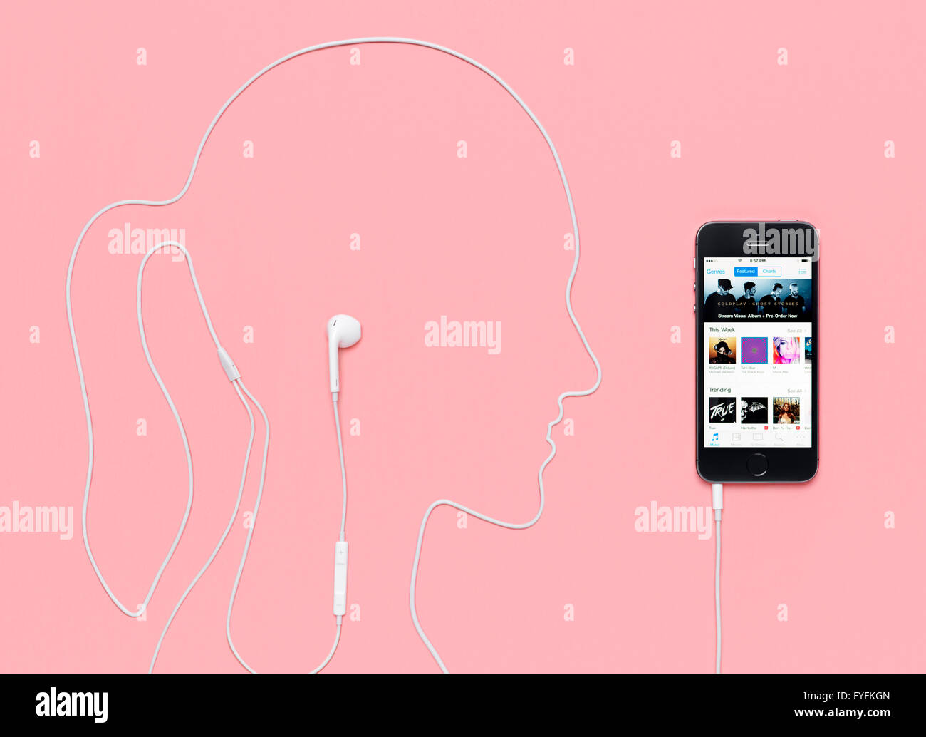 Headphone cable laid out in the shape of a woman's head plugged into an iPhone 5s displaying the iTunes music - Stock Image