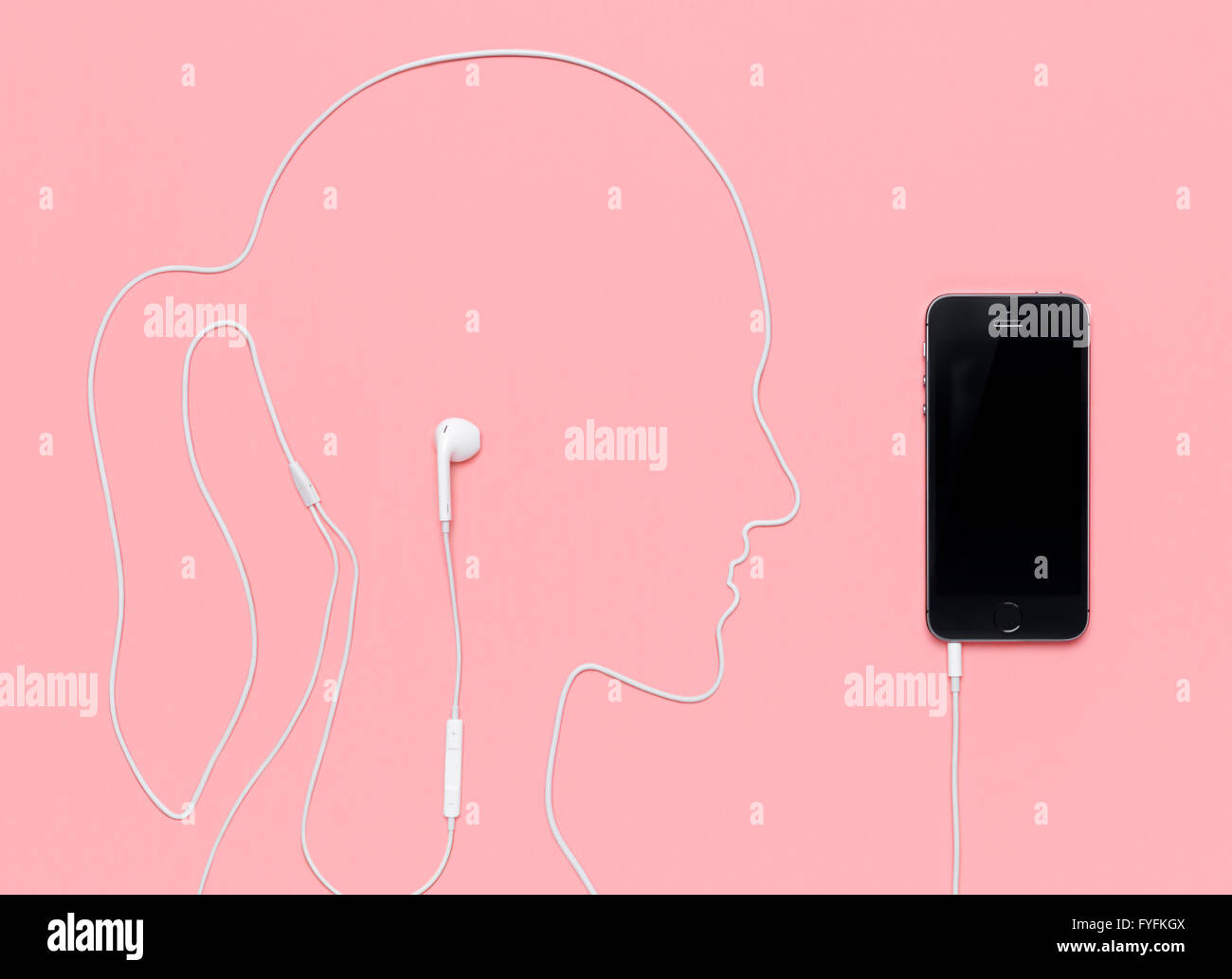Headphone cable laid out in the shape of a woman's head plugged into an iPhone 5s - Stock Image