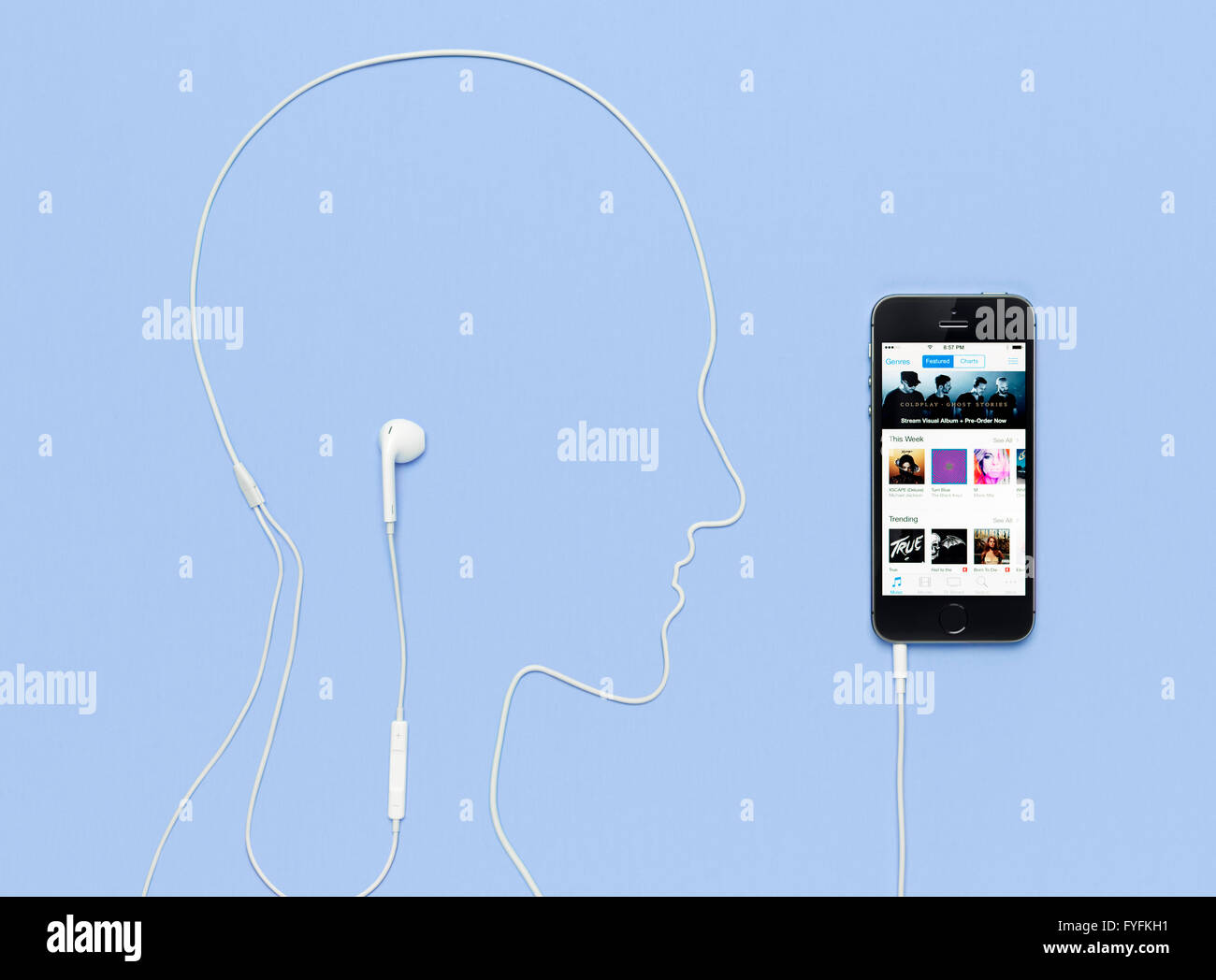 Headphone cable laid out in the shape of a man's head plugged into an iPhone 5s displaying the iTunes music - Stock Image