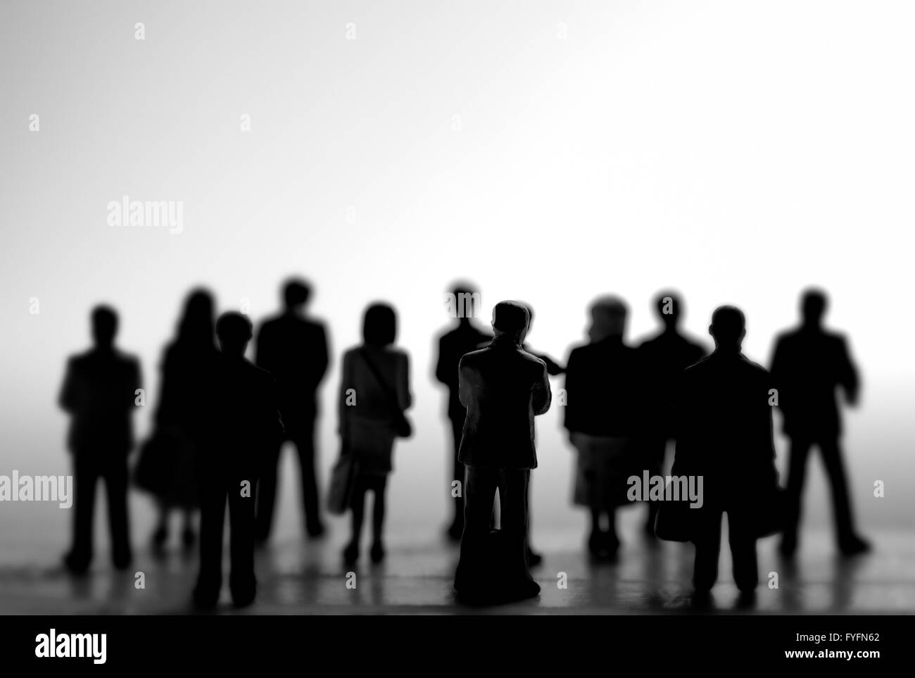 Crowdfunding concept. A crowd of miniature people standing in silhouette. - Stock Image
