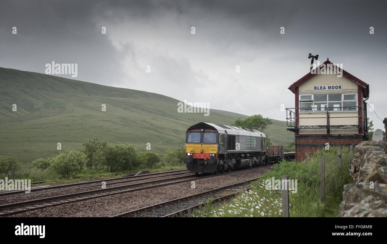 Carlisle, England - July 2, 2015: A Class 66 diesel locomotive hauling a freight train past the remove Blea Moor - Stock Image