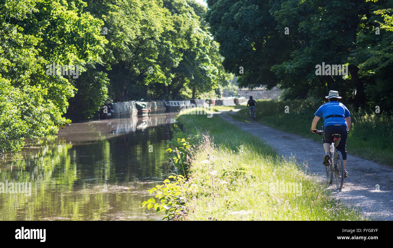 Leeds, England - June 30, 2015: Cyclists ride in the sunshine on the towpath of the Leeds and Liverpool Canal. - Stock Image