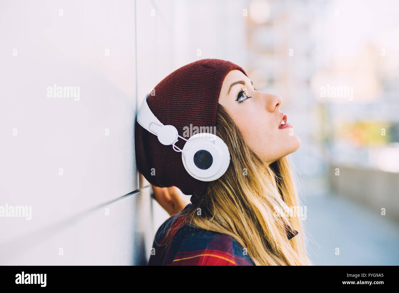 Half length profile portrait of young handsome caucasian blonde hair woman leaning against a wall, listening music - Stock Image