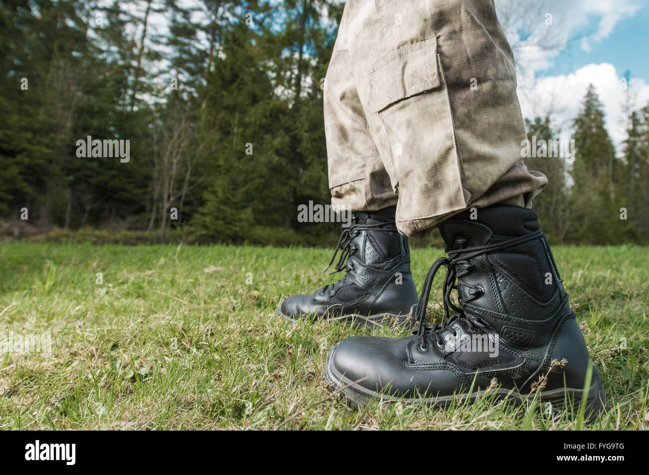 Poacher at Work Concept. Poacher Military Grade Shoes Closeup with Forest in the Background. - Stock Image