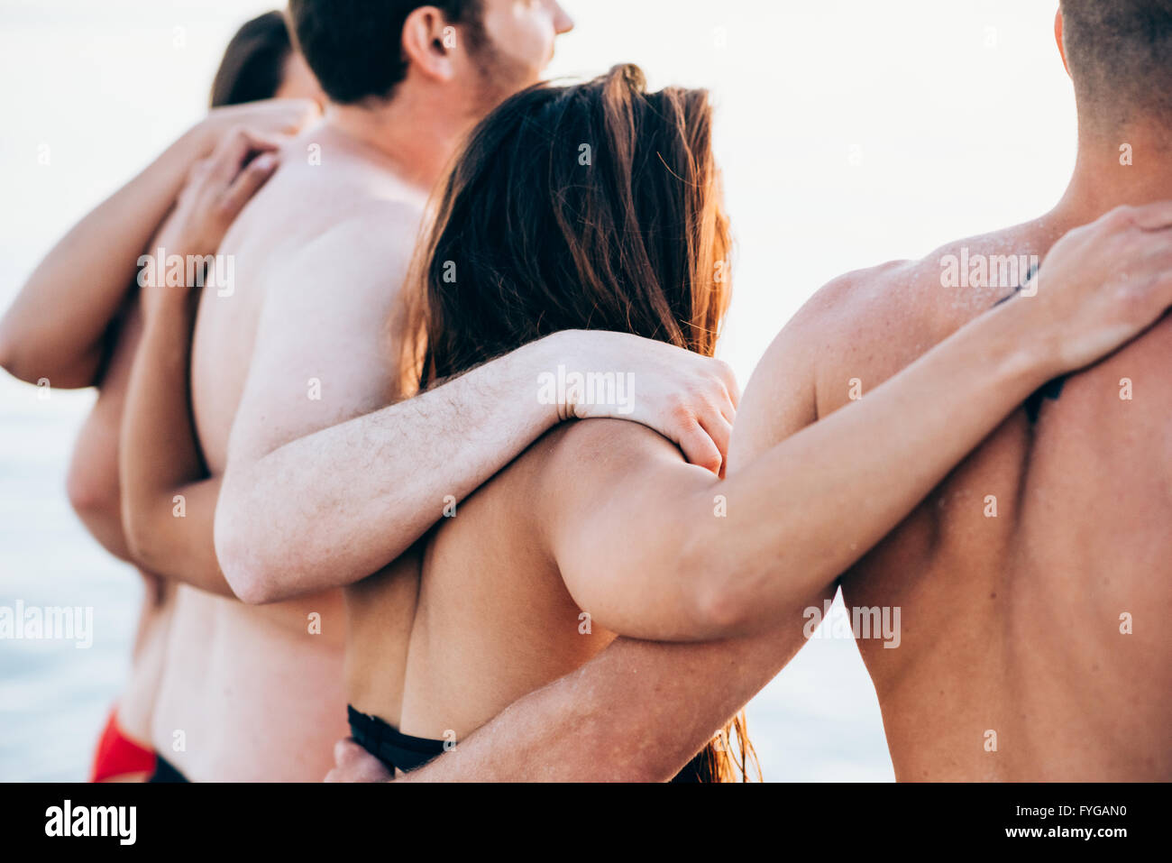 Rear view of group of young multiethnic friends women and men at the beach in summertime hugging - teamwork, friendship, - Stock Image