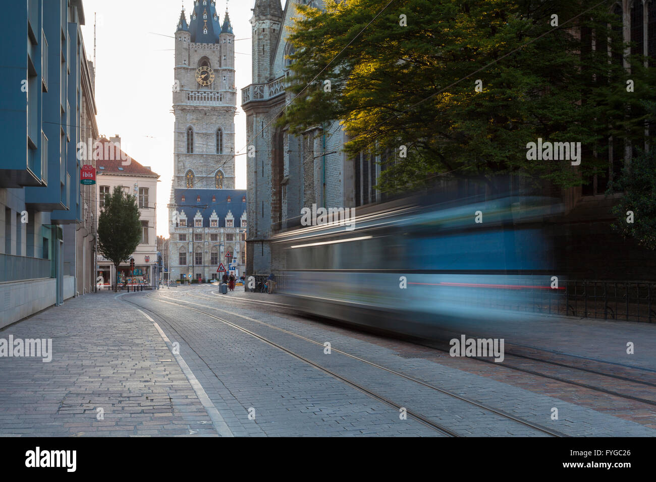 Historic buildings in the center of Ghent and trolley car in movement. - Stock Image