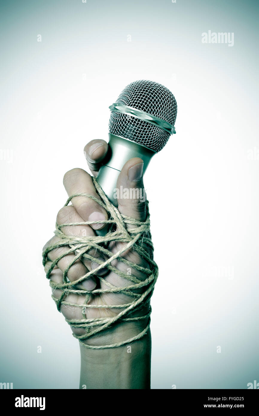 closeup of a microphone in the hand of a young man tied with rope, depicting the idea of the repression of the mass - Stock Image