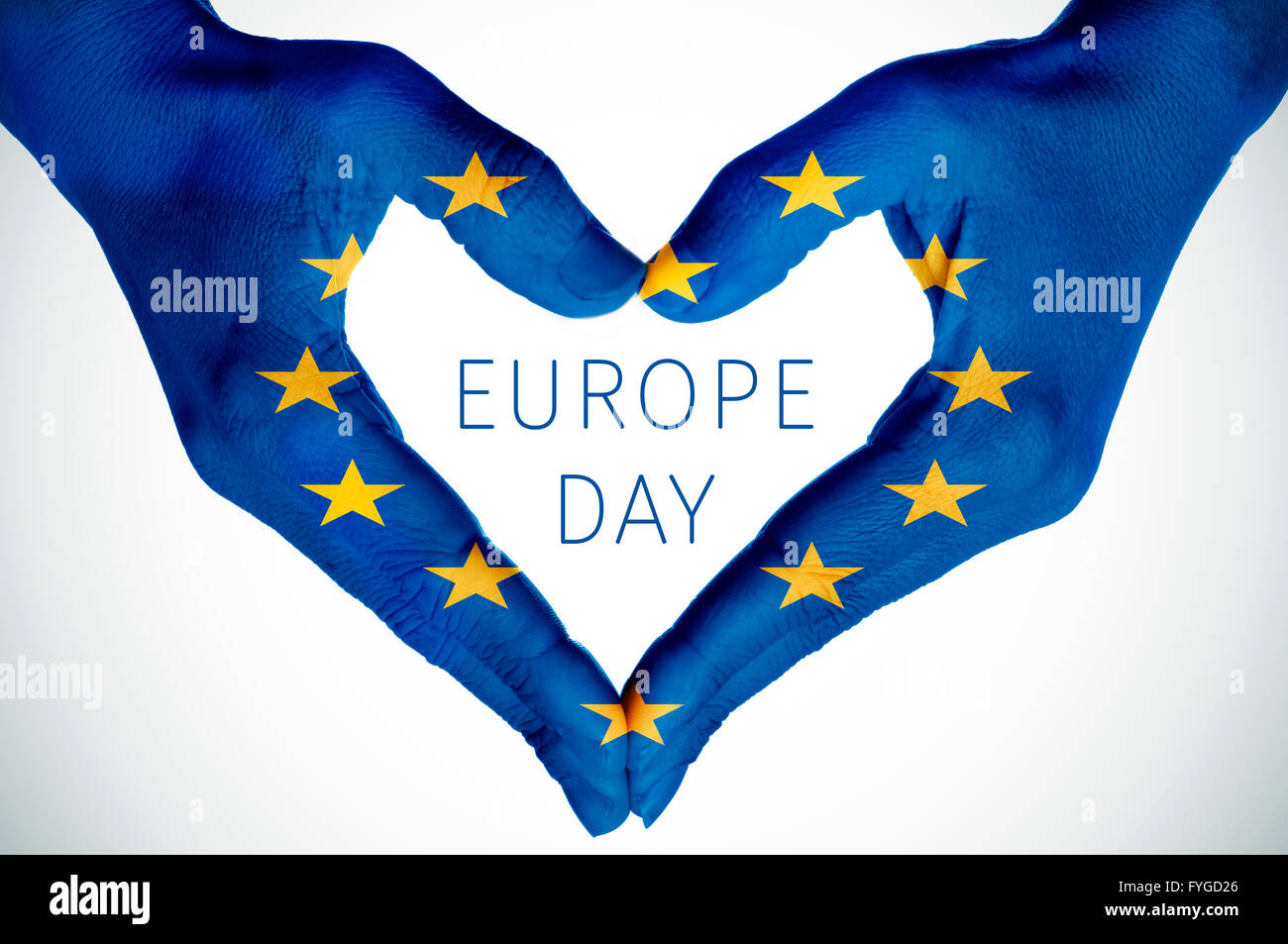 closeup of the hands of a young woman forming a heart patterned as the flag of the European Union and the text Europe - Stock Image