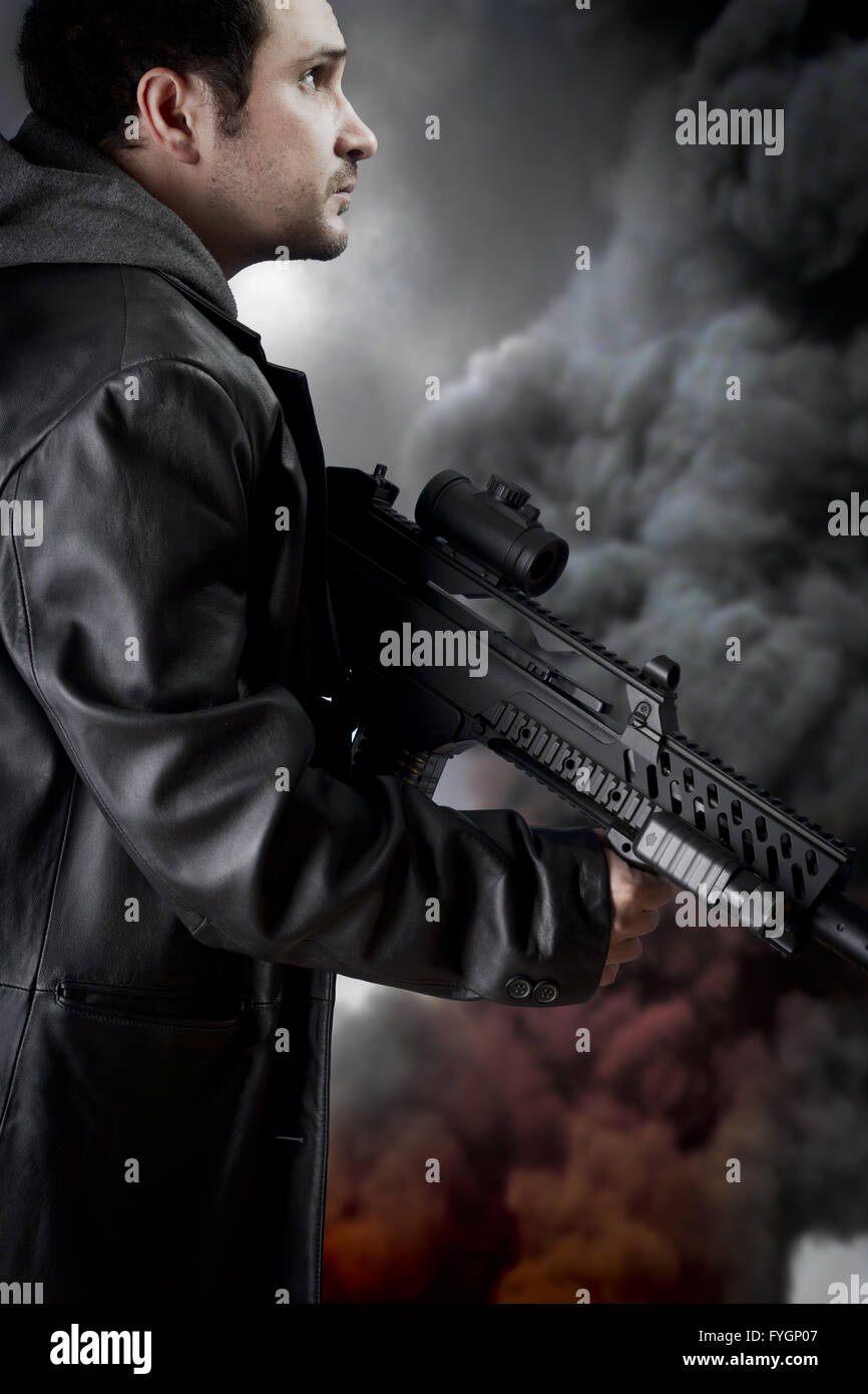 Man with long leather jacket and assault rifle, black smoke background Stock Photo