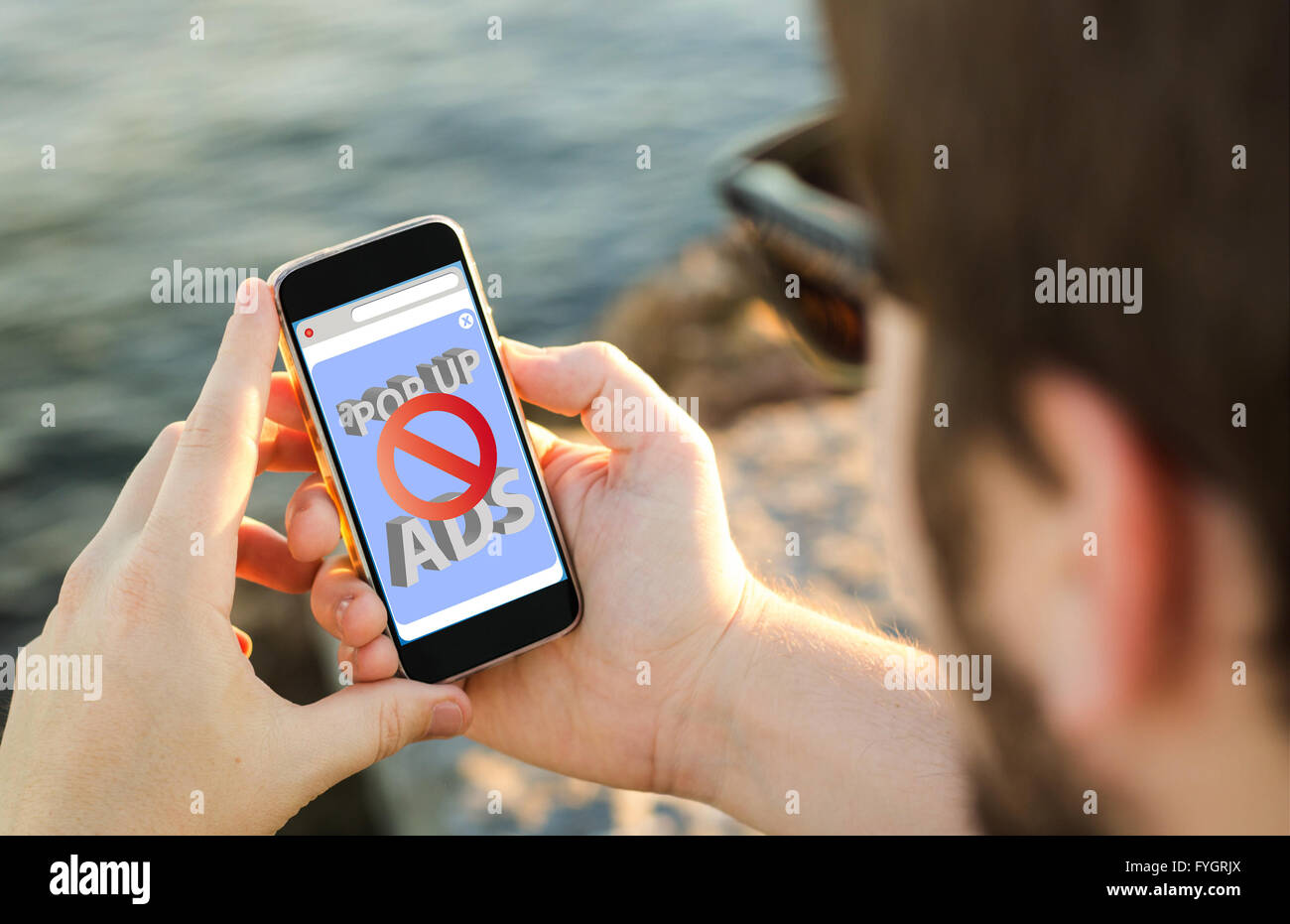 man on the coast using his smartphone with ads blocker. All screen graphics are made up. - Stock Image