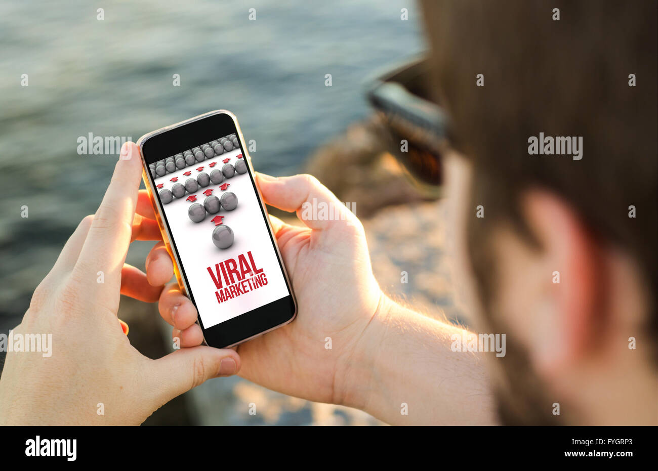 man on the coast using his smartphone showing viral marketing concept. All screen graphics are made up. - Stock Image