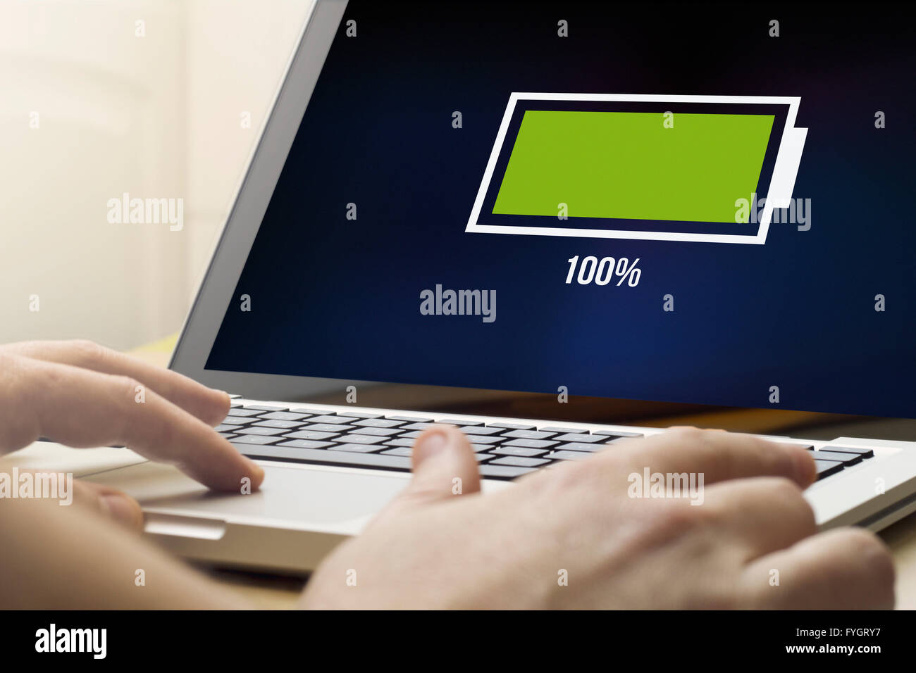 battery concept: man using a laptop with full battery on the screen. Screen graphics are made up. - Stock Image