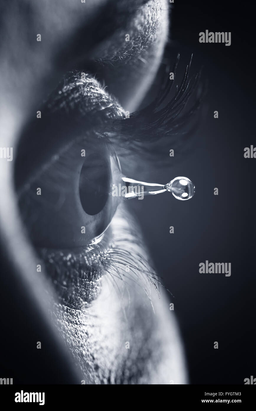 Eye health and vision concept. Pupil detail and tear water drop - Stock Image