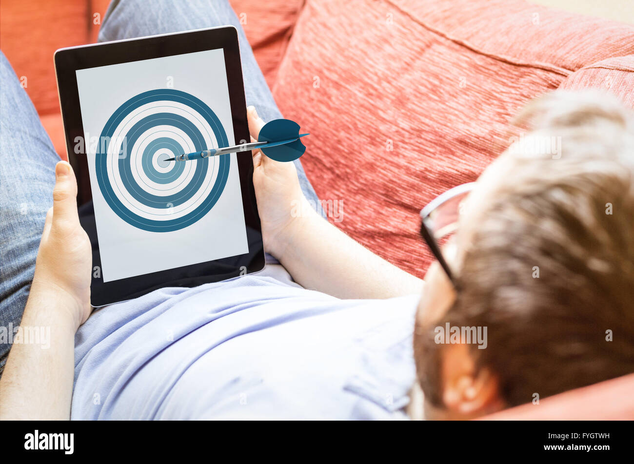 accuracy, business or mobile marketing concept: hipster on the sofa with dartboard tablet. Screen graphics are made - Stock Image