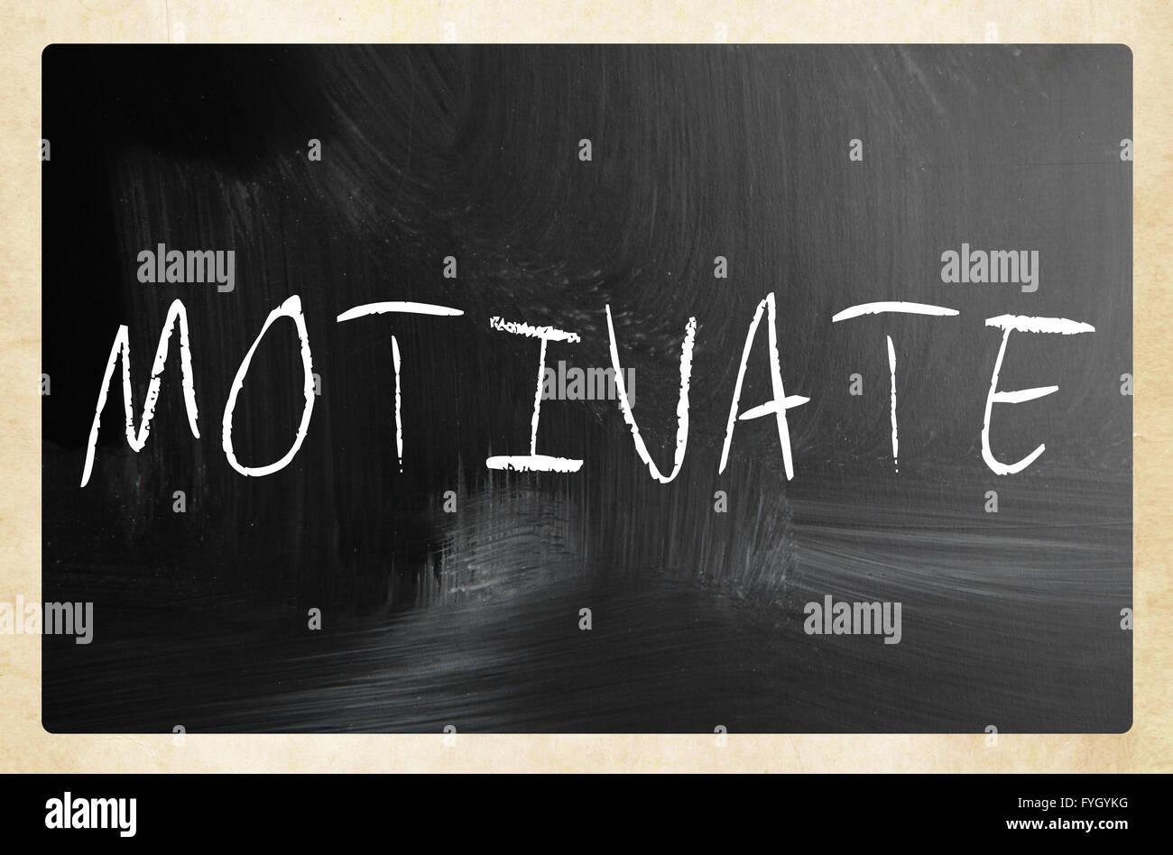motivate handwritten with white chalk on a blackboard - Stock Image