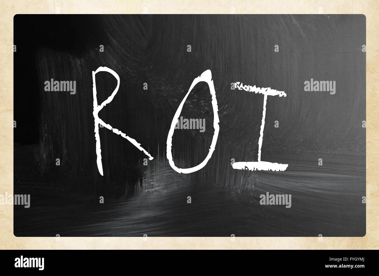 The word ROI handwritten with white chalk on a blackboard Stock Photo