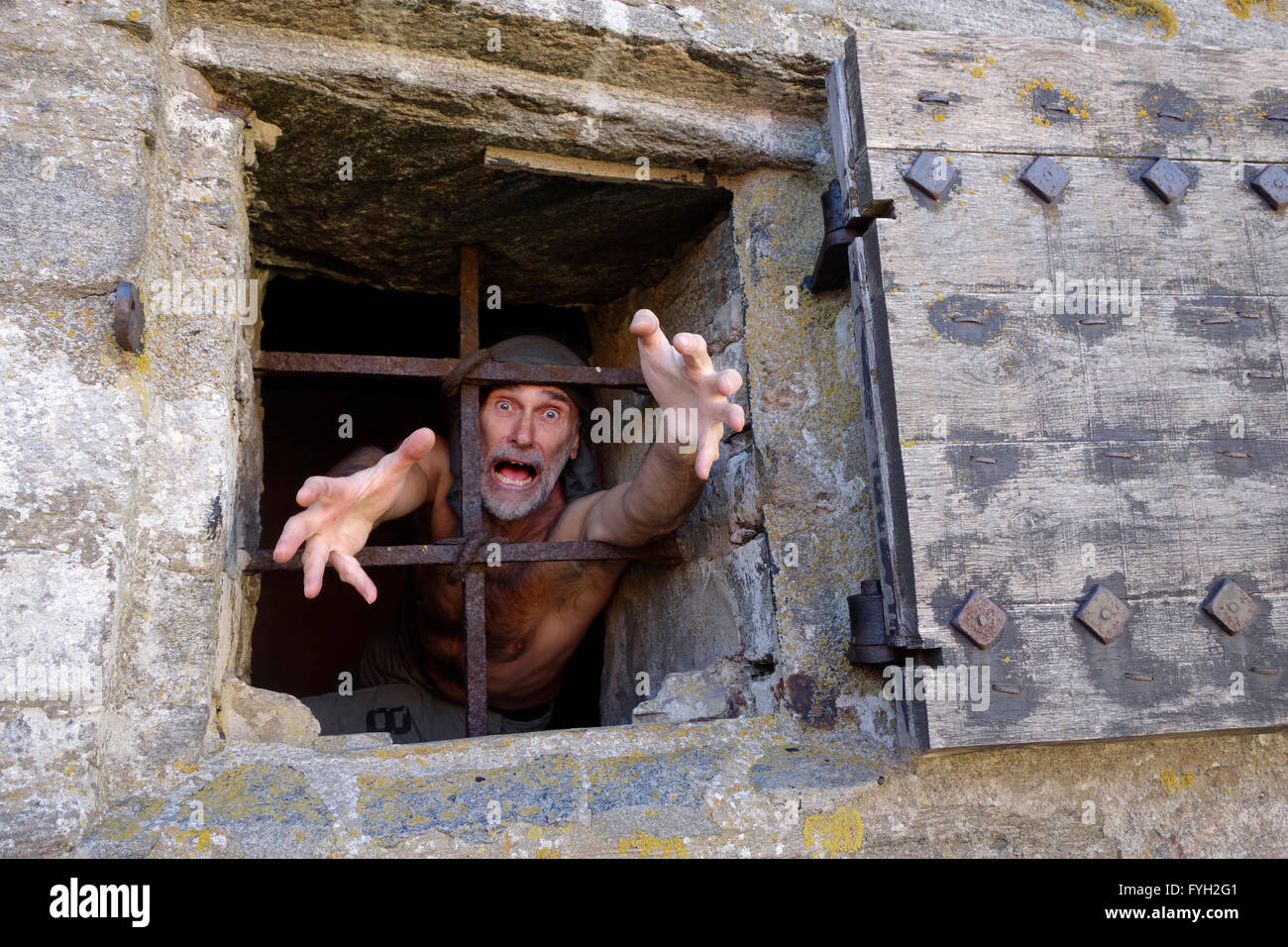 A man behind the window bars acts and overdramatizes a desperate prisoner. - Stock Image