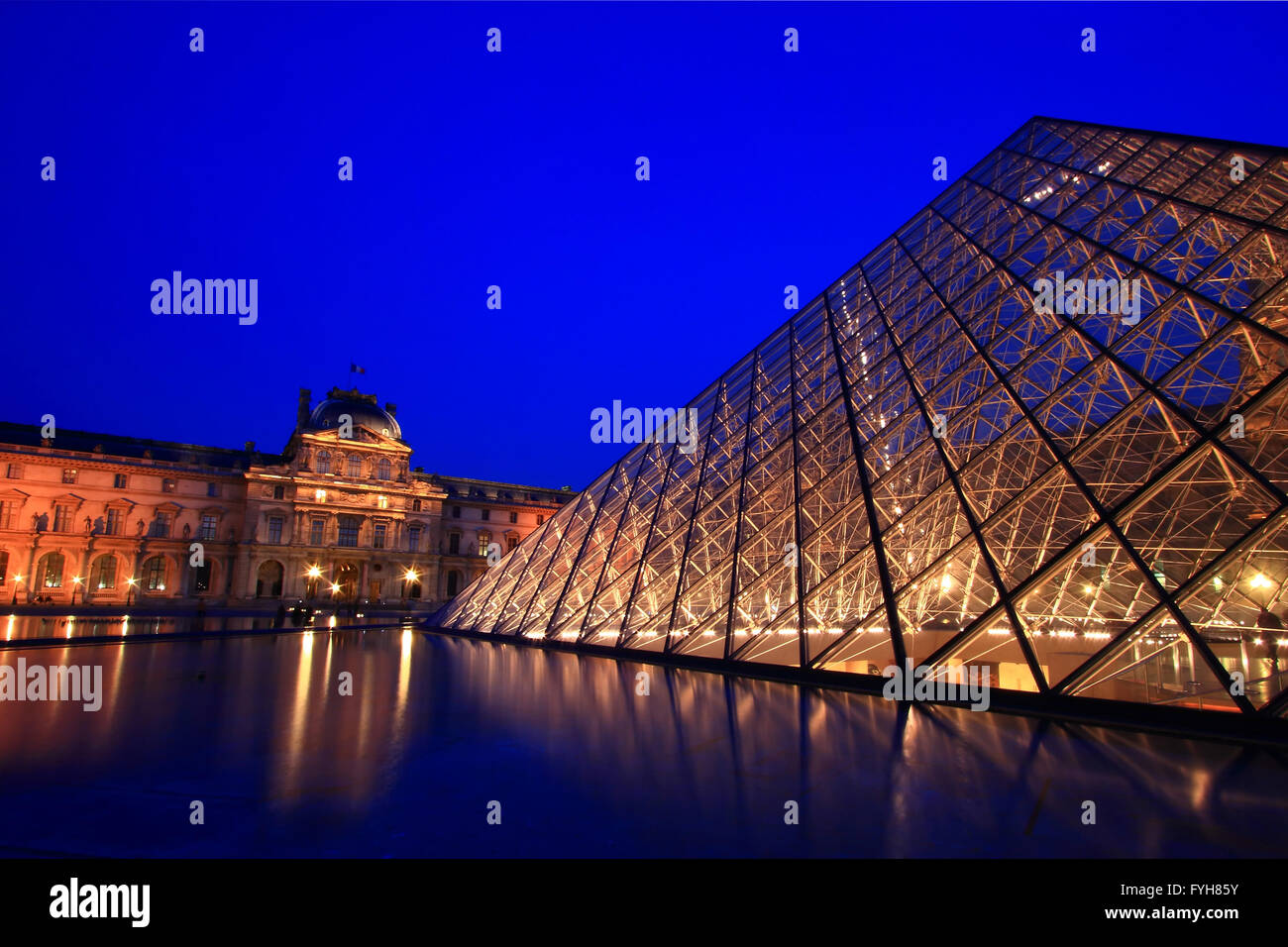 PARIS - APRIL 16: Closeup of Louvre Pyramid shines at dusk during the Summer Exhibition April 16 - Stock Image
