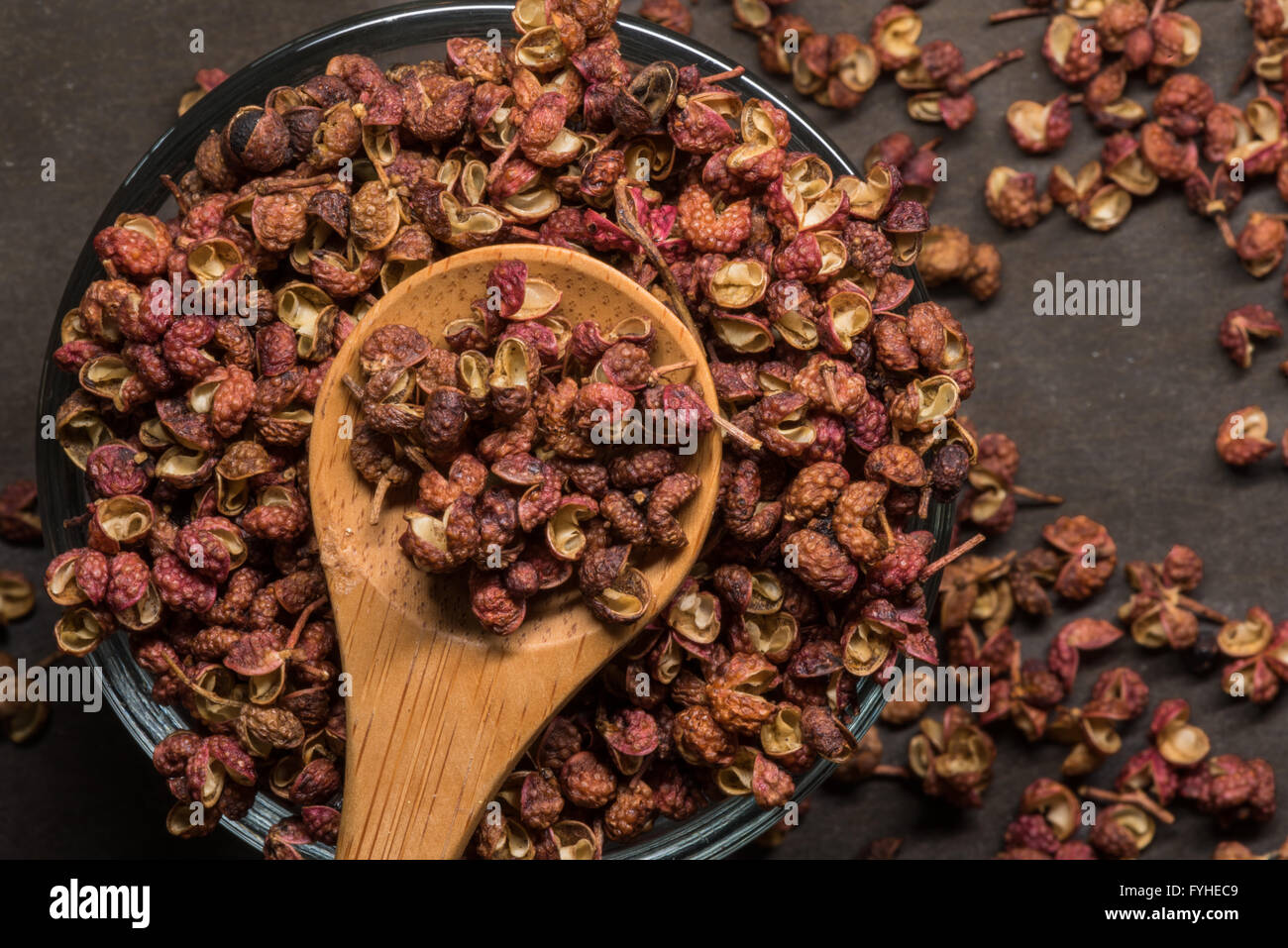 Szechuan Peppercorns in Wooden Spoon With Glass Bowl and spill over Stock Photo
