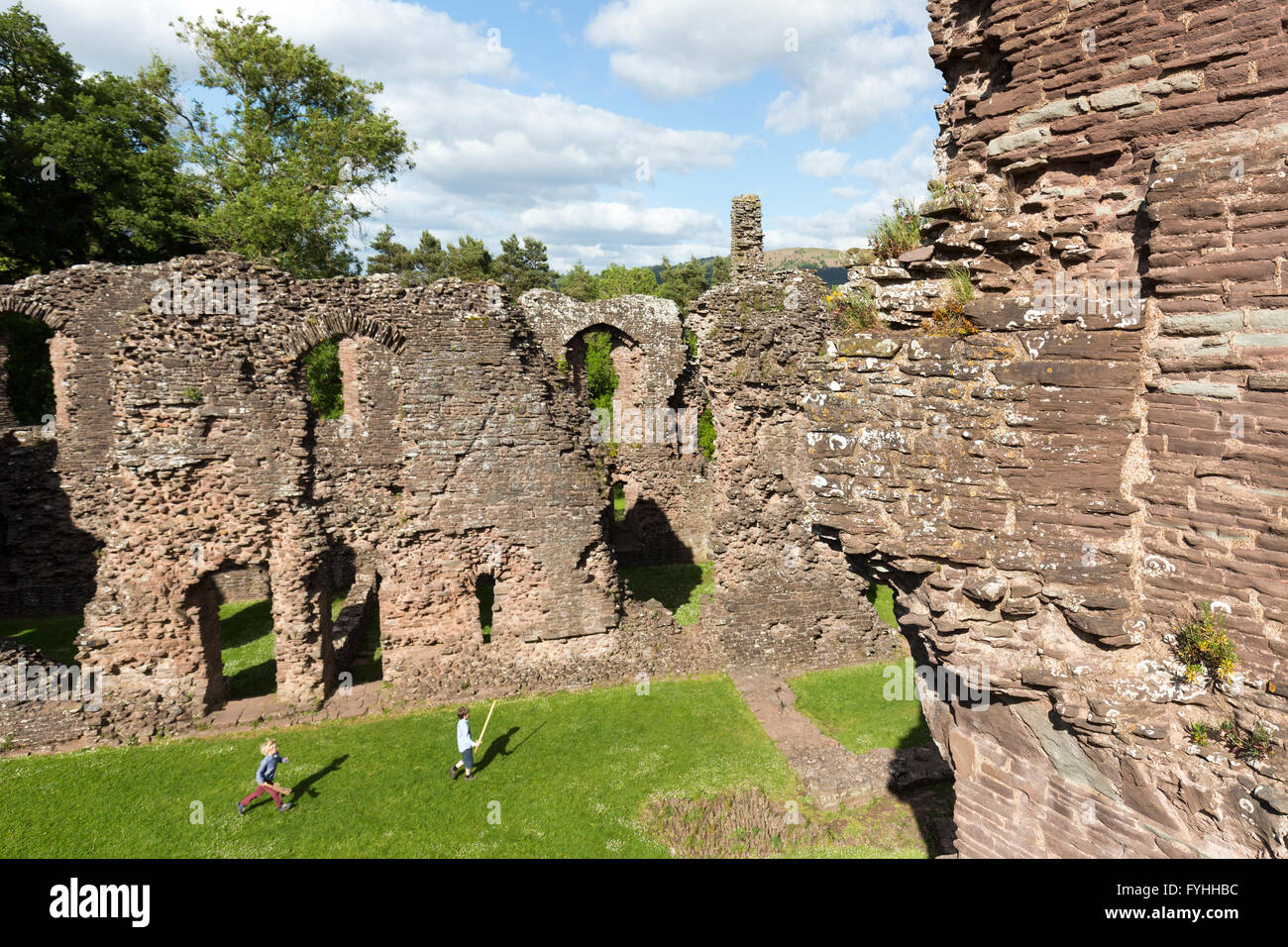 Two boys playing with toy swords in the ruined castle at Grosmont, Monmouthshire, Wales, UK - Stock Image