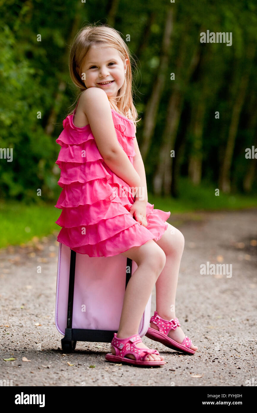 Little girl is sitting on her suitcase Stock Photo