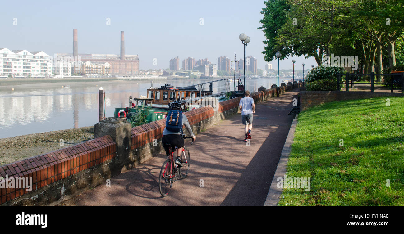 Unidentifiable cyclist and jogger on a path beside the River Thames in Battersea, London. - Stock Image