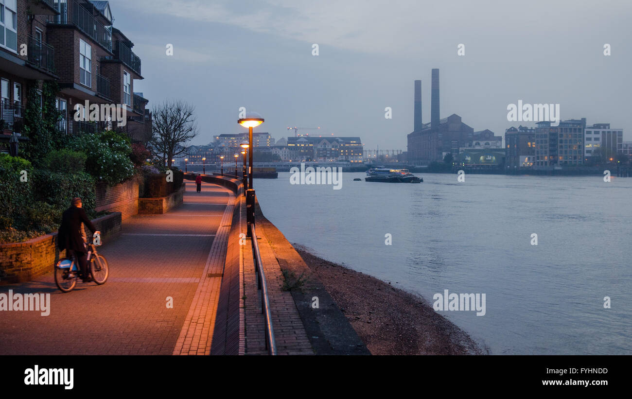 London, England - April 2, 2014: A man rides a 'Boris Bike' on the Thames Path in Battersea. Air pollution - Stock Image