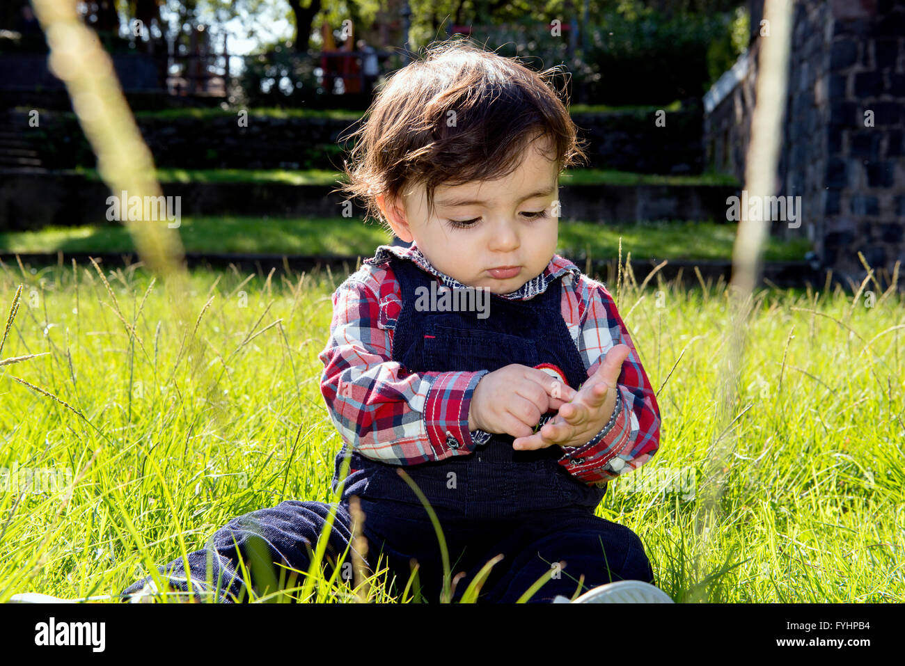 portrait of cute little boy one year old plays outside in the park